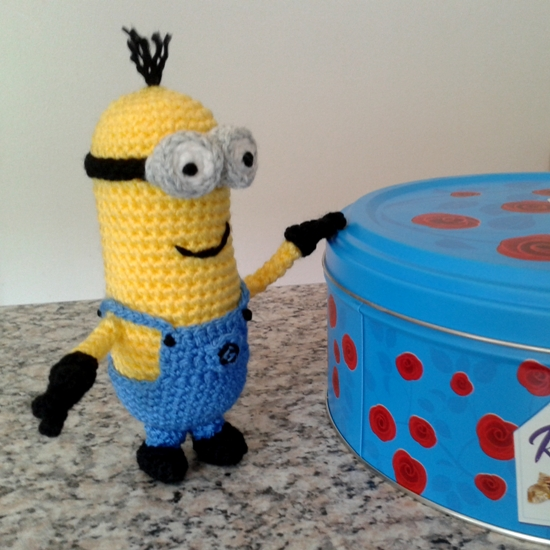 Kevin the crochet minion with a tin of chocolates